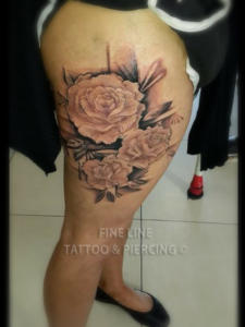Detailed roses on thigh tattoo