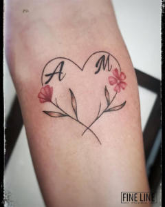 Children's initials in heart-shape flowers tattoo