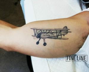 Realistic biplane tattoo